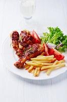 pernas de frango grelhado com batata frita e salada foto