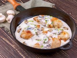 frigideira com peito de frango frito e cogumelos foto
