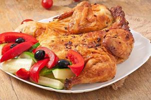 pequeno frango grelhado com legumes em um prato branco foto