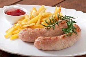 salsichas de frango grelhadas com um prato de batatas fritas foto