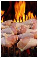 pernas de frango, grelha para churrasco e fogo