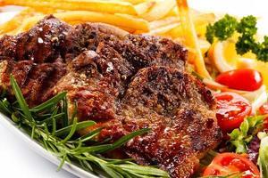 bifes grelhados, batatas fritas e legumes