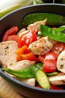 carne de peito de frango legumes na frigideira foto