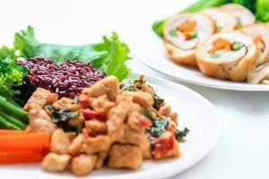 arroz coberto com frango frito e manjericão, foto