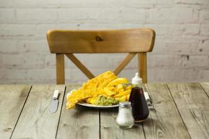 peixe britânico e batatas fritas em uma placa de impressão de jornal foto