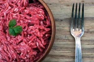 tigela de carne moída crua e garfo foto