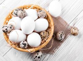 ovos de codorna e frango em uma cesta de vime foto