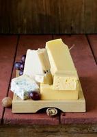 variedade de queijo, servida em uma placa de madeira com uvas