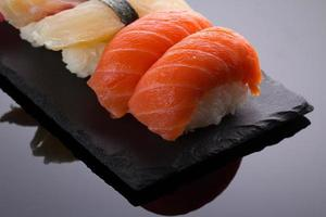 nigiri de sushi em um prato de pedra sobre fundo preto foto