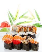 rolos de sushi e gunkans sobre fundo branco foto