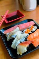 conjunto de sushi japonês no prato preto foto
