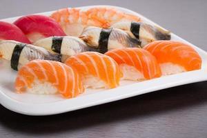 cozinha japonesa. conjunto de sushi nigiri na chapa branca. foto