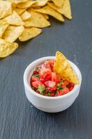 molho de salsa e nachos em tigela branca, fundo escuro de pedra