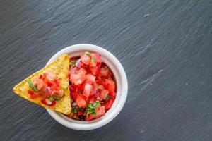 molho de salsa e nachos em tigela branca, fundo escuro de pedra foto