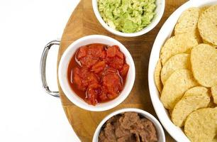 aperitivos de comida chips salsa feijão frito guacamole tábua de madeira