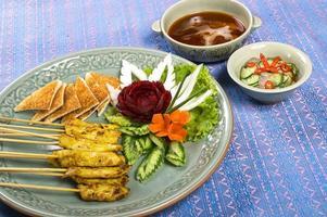 grelhados satay de porco com curry amarelo na vara de bambu foto