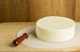 bloco redondo de queijo com faca foto