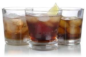 uísque, álcool e cola com cubos de gelo foto