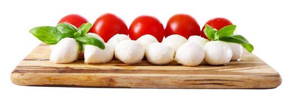 bolas de queijo mussarela saboroso com manjericão e tomate vermelho foto