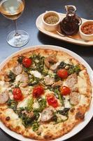 pizza paesana assada com um copo de vinho foto