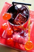 bebida vermelha com cubos de gelo e pinça preta