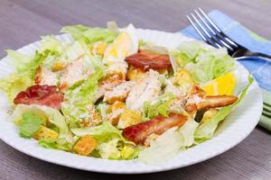 salada caesar com frango e pães foto