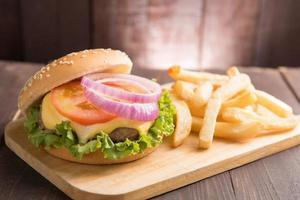 hambúrgueres de churrasco com batatas fritas no fundo de madeira