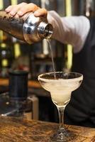 Braga no trabalho, preparando cocktails. derramando margarita em copo de coquetel.