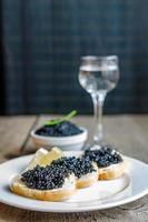 sanduíches com caviar preto e copo de vodka foto