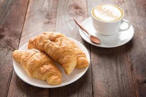 croissants cozidos frescos e café na mesa de madeira foto