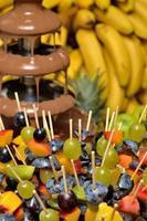 fonte de chocolate com espetos de frutas foto