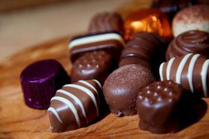 chocolates de leite, brancos e escuros sobre um fundo de madeira natural. foto