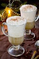 cappuccino com uma árvore de Natal decorada em uma mesa de madeira foto