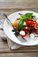 salada caprese em um prato branco foto