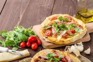 pizza italiana com queijo parmesão, presunto e rúcula