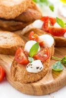 bruschetta com mussarela, manjericão e tomate cereja, vertical foto