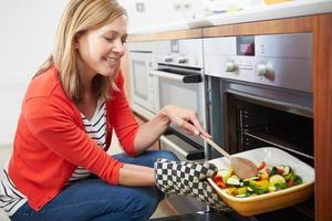 mulher colocando bandeja de legumes assados no forno foto