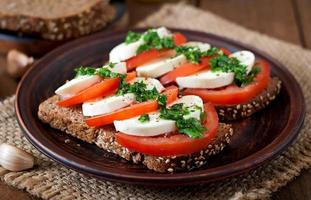 sanduíches dietéticos úteis com mussarela, tomate e pão de centeio foto