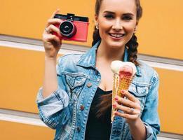 menina bonita posando com câmera vintage e sorvete multicolorido foto