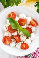 salada com mussarela, manjericão e tomate cereja, vertical foto