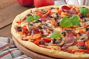 pizza com presunto, cogumelos e azeitonas foto