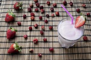 milk-shake de morango com morangos no fundo foto