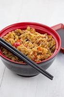 arroz tailandês com legumes em um fundo de madeira foto