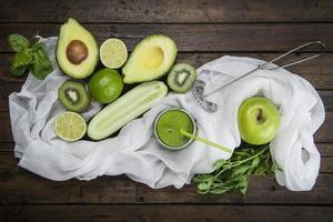 frutas e legumes com um copo de suco verde foto