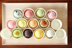 colher de sorvete doce e colorido na placa de madeira foto