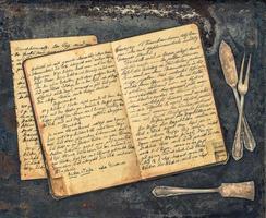 talheres antigos e livro de receitas manuscritas vintage foto