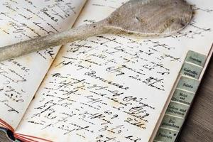 livro de receitas antigo com colher de pau foto