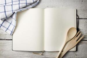 livro de receitas em branco na mesa de madeira foto