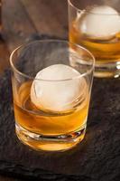 uísque de bourbon com um cubo de gelo de esfera