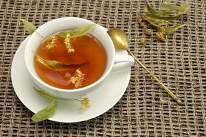 xícara de chá com chá de ervas e colher na toalha da mesa
